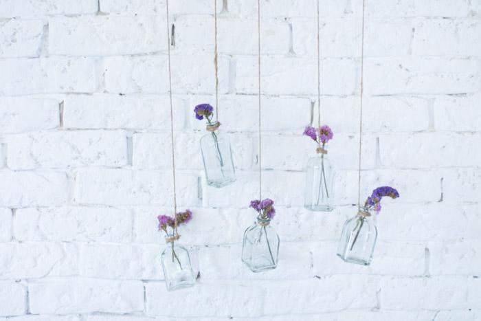 Rama con botellas de cristal y flores diy